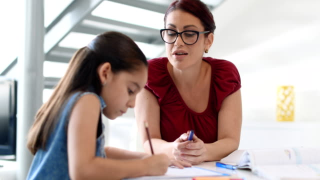 Education With Mom Helping Daughter Doing School Homework At Home Happy white family at home. Hispanic mother and female child. Latina mom helping daughter with school homework. Education, people, motherhood and relationship, woman teaching and girl learning elementary age stock videos & royalty-free footage