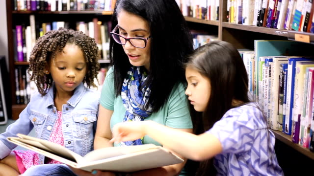 Education.Librarian reads book to elementary students in library or classroom. Latin descent teacher or librarian reads a book to a multi-ethnic group of elementary age students in school classroom or library setting. elementary age stock videos & royalty-free footage