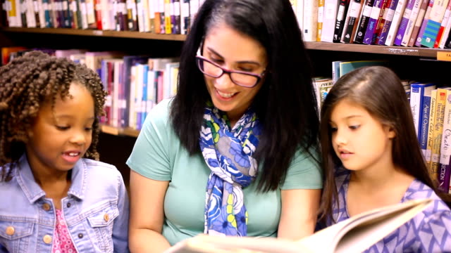 Education.Librarian reads book to elementary students in library or classroom. video