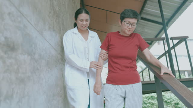Effort of senior mother trying to move down stair with doctor-stock video video