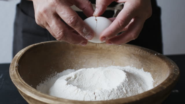 Egg falls on wooden bowl with flour. Slow motion shot of egg falls on wooden bowl with flour. ingredient stock videos & royalty-free footage