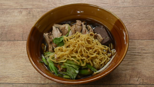 egg noodles with boiled duck in Chinese herb brown soup picking by chopsticks to eat