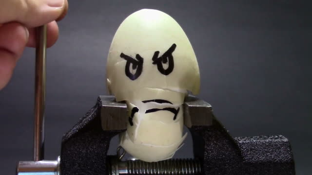 Egg with sad face painted on it being crushed between the arm  of a metallic vice, conceptual footage about stress and health related problems video