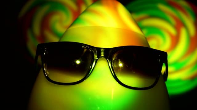 egghead man in sunglasses in the multicolored spotlight video