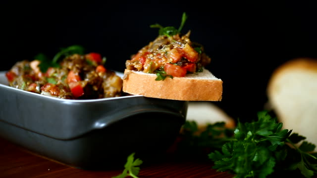 eggplant caviar with tomatoes and a slice of bread eggplant caviar with tomatoes and a slice of bread on a wooden table salad bowl stock videos & royalty-free footage