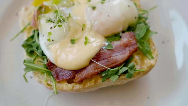 Eggs Benedict with bread and tomato on a plate with becon morning sandwich video