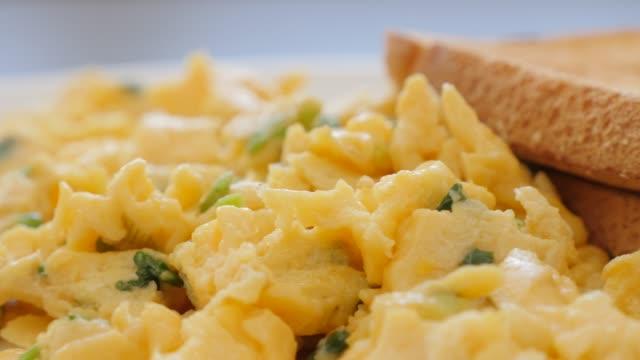stockvideo's en b-roll-footage met eieren gebakken en vermengd met lente uitjes op plaat met toast brood slow pannen 4k - geroosterd brood