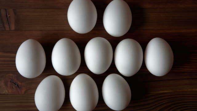 Eggs on wooden background. View from above. Stop Motion.