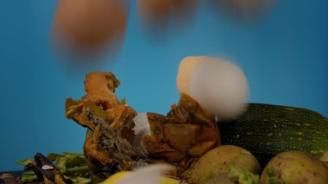 Eggshells fall on a pile of compost, safe food waste recycling, slow motion video