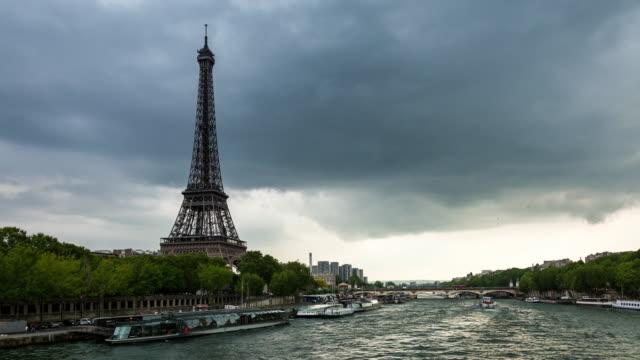 eiffeltornet och floden seine mörka moln dag timelapse - turistbåt bildbanksvideor och videomaterial från bakom kulisserna