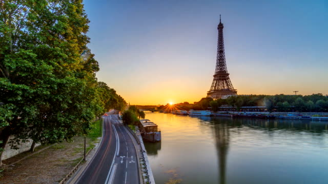 Eiffel Tower and the Seine river at Sunrise timelapse, Paris, France Eiffel Tower and the Seine river at Sunrise timelapse, Paris, France. Morning view from Bir-Hakeim bridge with reflections on water and traffic on the street european culture stock videos & royalty-free footage