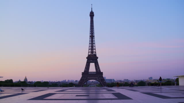 Eiffel tower at sunset orange blue sky in Paris during the summer. Haussmanian buildings, trees, 16th, symbol, trocadero, architecture, landmark, historic, birds. Tracking in 4K UHD. Eiffel tower at sunset orange blue sky in Paris during the summer. Haussmanian buildings, trees, 16th, symbol, trocadero, architecture, landmark, historic, birds. Tracking in 4K UHD. french architecture stock videos & royalty-free footage