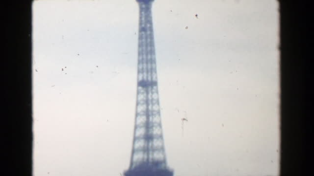 1949: eiffel tower view man wanting picture taken at historic monument. - paris fashion stock videos & royalty-free footage