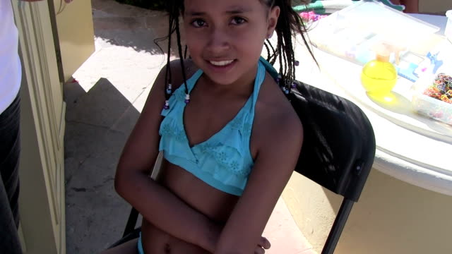 stockvideo's en b-roll-footage met eight year old mexican girl getting her hair braided - gevlochten haar