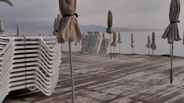 エイラットビーチ。空のビーチラウンジャーのミディアムショットが互いに1つ、リゾートの傘を閉じた - 人の居住地点の映像素材/bロール