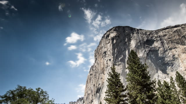 El Capitan Looming Over Yosemite - Time Lapse El Capitan, one of the two most famous granite cliff faces in Yosemite National park. This vertical granite cliff stands about 900m high over the valley floor. national landmark stock videos & royalty-free footage