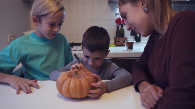 Elder children looking their small brother drawing on pumpkin video