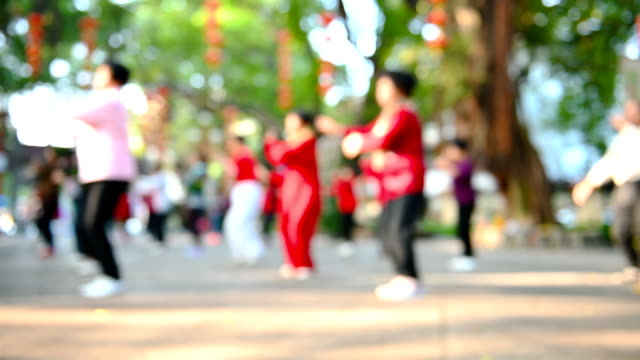 elder Chinese people doing Tai Ji exercise in a park in the morning at blurred focus as background - vídeo