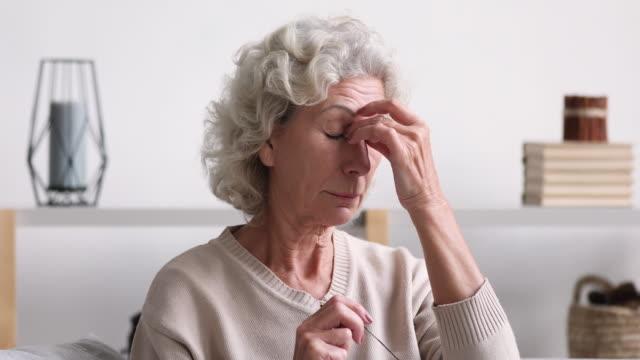Elder lady rubbing tired dry eyes feeling eye strain
