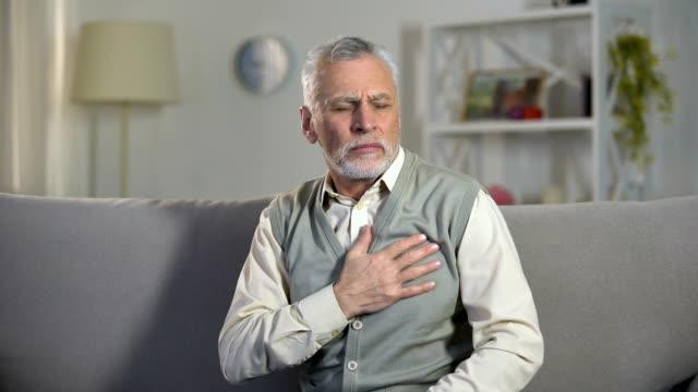 stockvideo's en b-roll-footage met ouderling man gevoel scherpe pijn in borst en rug, risico op een hartaanval, cardiologie - gewichten