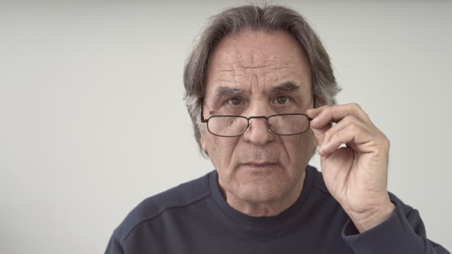 elder man looking detail, holding glasses - curiosità video stock e b–roll