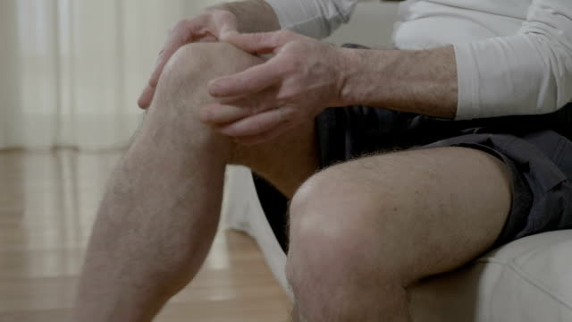 Elder man suffering from rheumatic pain disease rubbing his sore and painful knee doing herself massage therapy Elder man suffering from rheumatic pain disease rubbing his sore and painful knee doing herself massage therapy knee stock videos & royalty-free footage