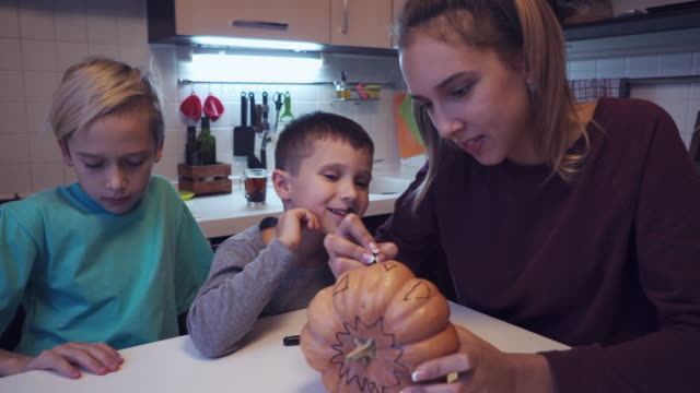 Elder sister teaching small brother to draw on halloween pumpkin video