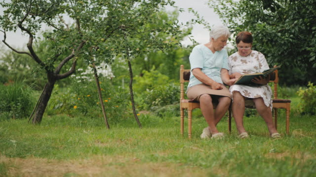 elder sister women view photos in old family album - bench stock videos & royalty-free footage