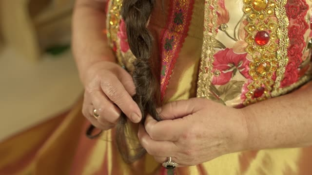 Elder woman in traditional russian clothes hands braiding hair video
