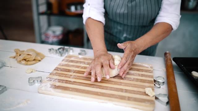 vídeos de stock e filmes b-roll de elder woman is kneading dough on the table - baking bread at home