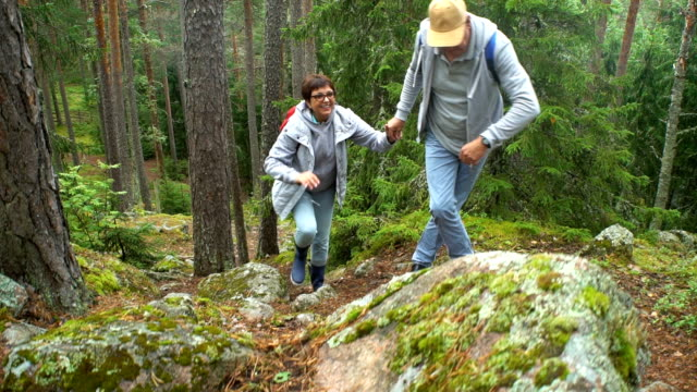 Elderly active couple climbing on the rock in the northern forest