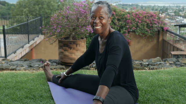 Elderly African American smiling woman stretching her legs sitting on a yoga mat video