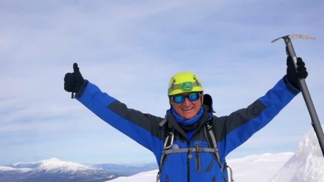 äldre alpin klättrare bor armar öppen i toppen av hög höjd berget på vintern vid soluppgången - vintersport bildbanksvideor och videomaterial från bakom kulisserna