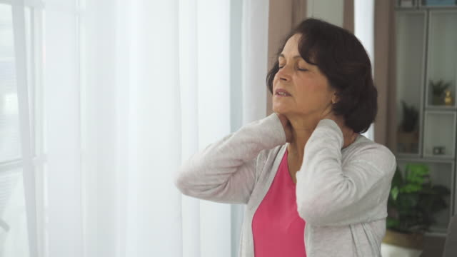 Elderly american woman massage neck with hand standing in apartment room