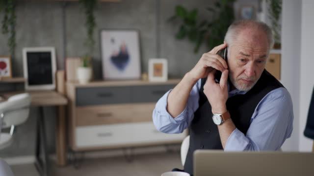 dizüstü bilgisayar kullanan ve akıllı telefonda konuşan yaşlı mimar - kulak i̇çi kulaklık stok videoları ve detay görüntü çekimi