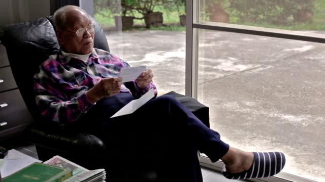 Elderly Asian man reading a letter video