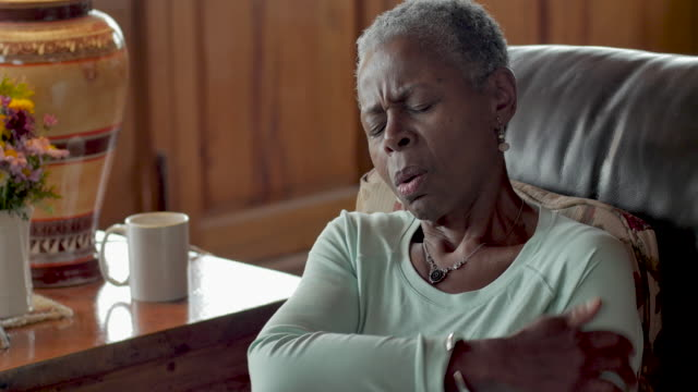Elderly black woman in pain puts an ice pack on her shoulder