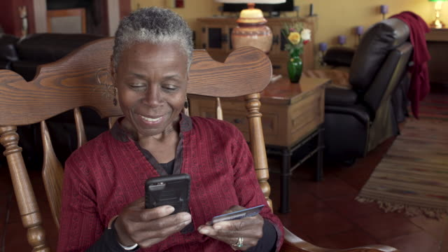 Elderly black woman paying for her mobile phone purchase with a credit card