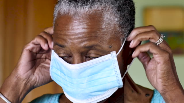 Elderly black woman puts on a respiratory face mask in her home