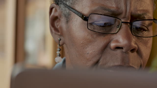 elderly black woman reading bad news while looking at a computer monitor - rabbia emozione negativa video stock e b–roll