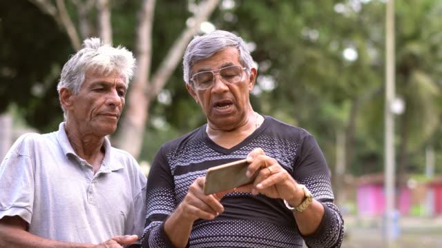 elderly brothers using smart phone - surfować po internecie filmów i materiałów b-roll