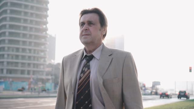 ビジネススーツとブリーフケースでネクタイを着た高齢のビジネスマンは、日没時に交通量の多い道路の近くに行きます ビデオ