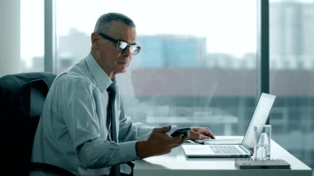 älteren Geschäftsmann Blick auf Telefon und arbeiten mit Computer im modernen Büro – Video