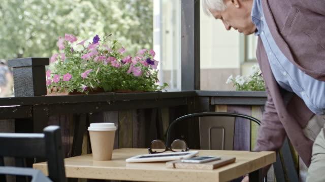 Elderly Businessman Reading from Digital Tablet in Cafe video