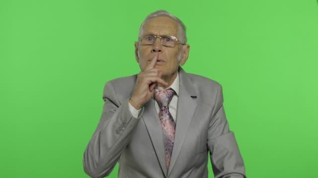 elderly businessman showing silence gesture. senior man showing shh gesture - cisza filmów i materiałów b-roll
