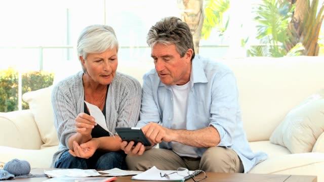 Elderly couple calculating their bills video