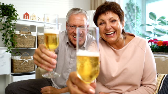 Elderly Couple Connected with Friends using Laptop Video Call Camera and Drinking Champagne video