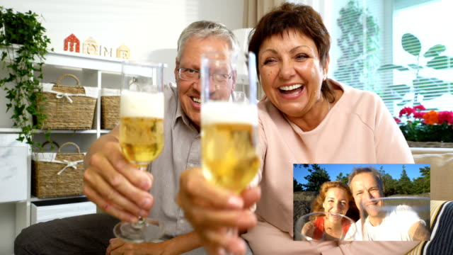 Elderly Couple Connected with their adult children using Laptop Video Call Camera and Drinking Champagne video