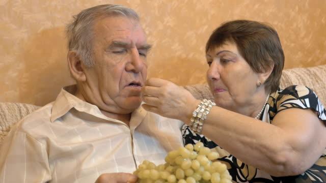 Elderly couple eating grape berries. video