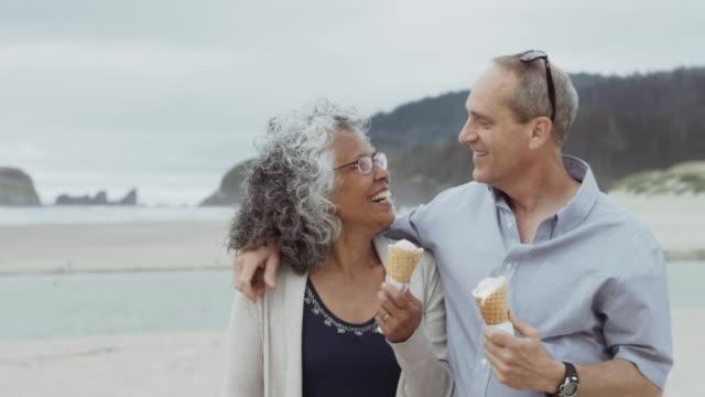 vídeos de stock e filmes b-roll de elderly couple eating ice cream at the beach - comida doce